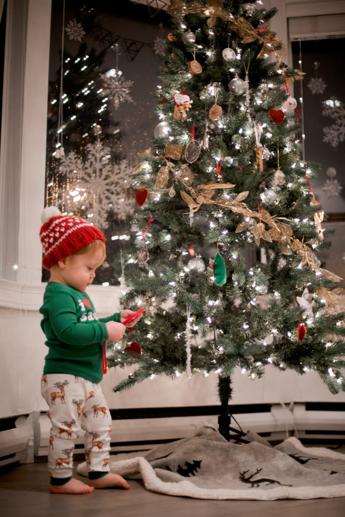 toddler looking at tree ornaments