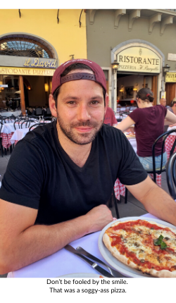 Broad World's boyfriend smiles and poses with pizza in Florence.