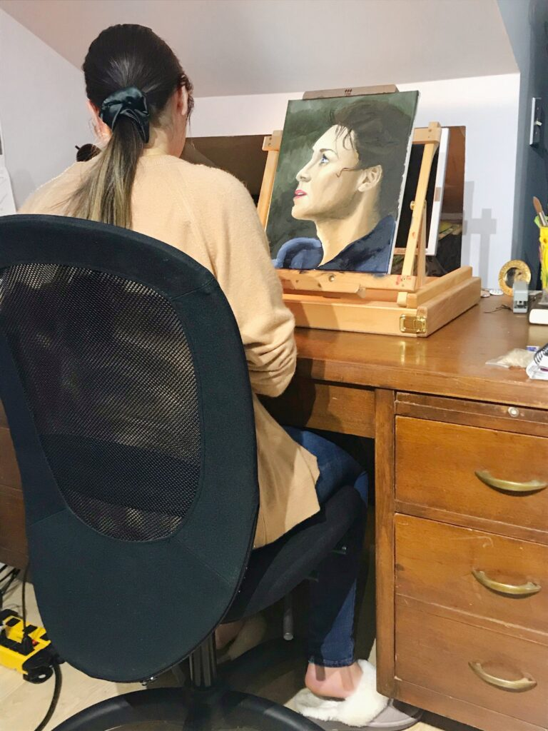 High school student, Mackenzie, paints a portrait with oil based paints.
